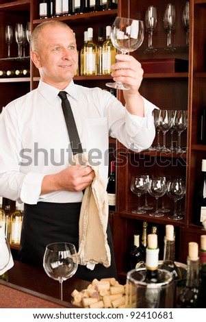 Wine bar waiter looking at clean glass in restaurant