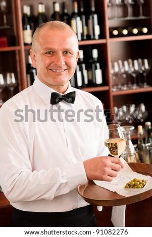 Wine bar waiter mature serving on tray glass olives restaurant - stock photo