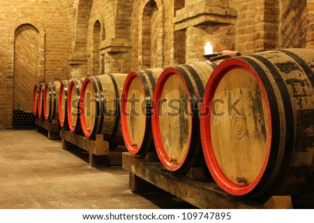 Wine barrels and bottles in a vineyard cellar with a lighting candle. The picture was taken in Csopak, Balaton, Hungary - stock photo