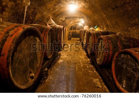 Wine barrels and bottles in the back in a cellar . Warm colors, wide angle view. - stock photo
