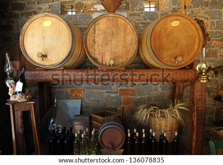 Wine barrels and bottles in the old cellar of a winery. - stock photo
