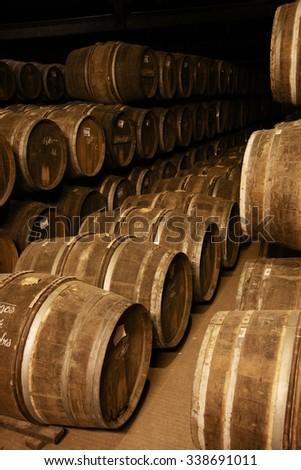 Wine barrels in a dark old cellar - stock photo