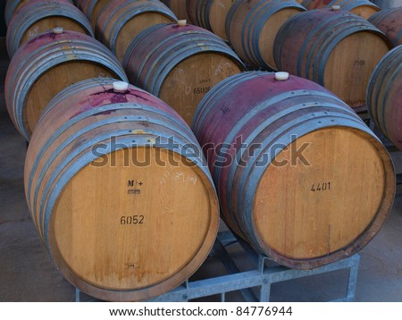 Wine barrels in arrangement waiting in a cellar - stock photo