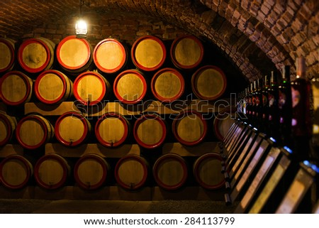 Wine barrels in the antique cellar. Cavernous wine cellar with stacked oak barrels for maturing red wine. Selective focus - stock photo