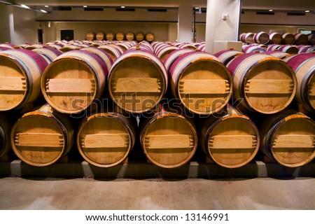 Wine barrels in winery cellar - stock photo
