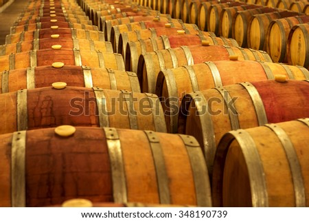 Wine barrels stacked in the cellar of the winery. - stock photo