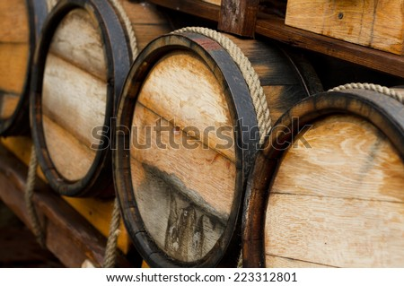 Wine barrels stacked in the old cellar  - stock photo
