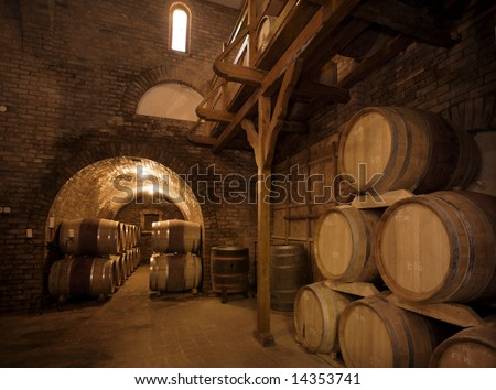 Wine barrels stacked in the old cellar of the vinery. - stock photo