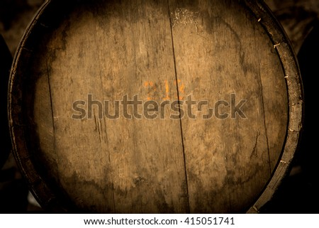 Wine barrels stacked in the old cellar of the winery.Detail. - stock photo