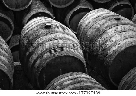 wine barrels stacked in winery in white and black - stock photo
