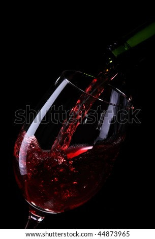wine being poured into a glass on black - stock photo
