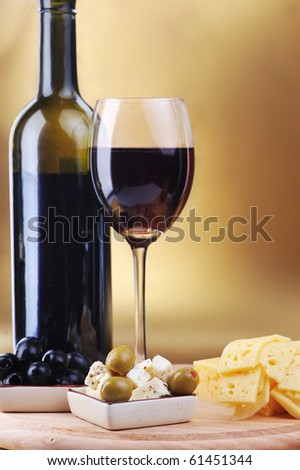 wine bottle and cheese on gold background - stock photo