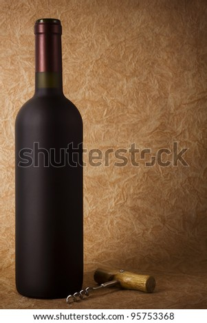 wine bottle and corkscrew on a paper background - stock photo