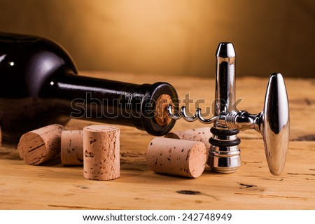 wine bottle and corkscrew on table - stock photo