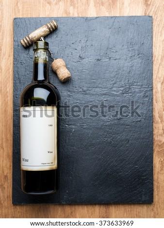 Wine bottle and corkscrew on the graphite board. - stock photo