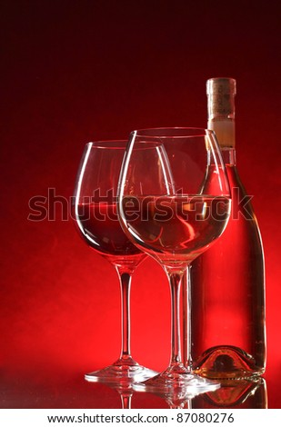 wine bottle and glasses on red background