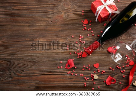 Wine bottle and glasses with handmade hearts on wooden background - stock photo