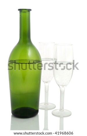 Wine bottle and pair of champagne flutes against a white background - stock photo