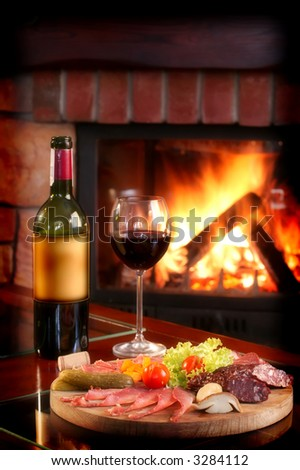 Wine bottle and partially filled glass with assorted food on a wooden serving plate - stock photo