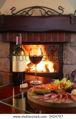 Wine bottle and partially filled glass with assorted food on a wooden serving plate. - stock photo
