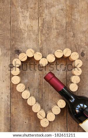 Wine bottle and wine cork on old wooden board (copy space for text on top part) - stock photo