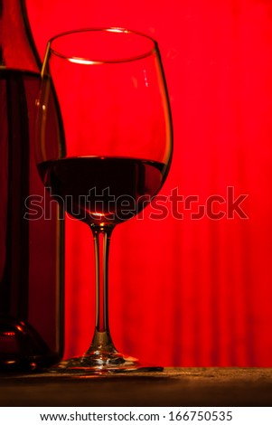 wine bottle and wine glass together on wooden table