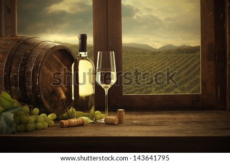 Wine bottle and wineglass on wooden table, vineyard on background - stock photo