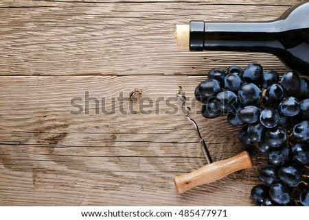 Wine bottle, corkscrew and grape on wooden table top view
