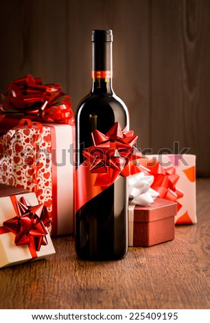 Wine bottle gift with red ribbon and colorful christmas gift boxes on wooden table. - stock photo