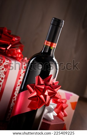 Wine bottle gift with red ribbon and gift boxes on wooden background. - stock photo