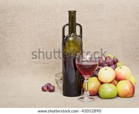 Wine bottle, glass and fruit on canvas - a still-life - stock photo