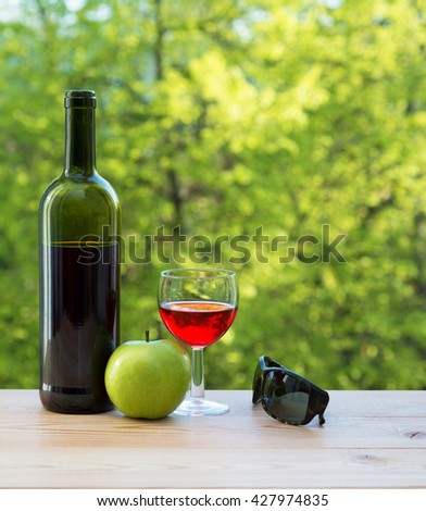 wine bottle, glass green apple and sunglasses on table in the garden - stock photo