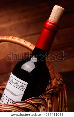 Wine bottle in a basket on wooden table, label is self made - stock photo