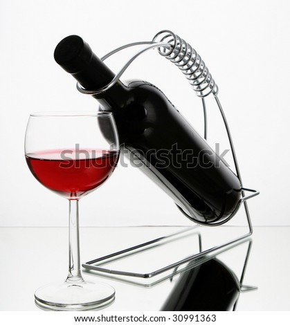 wine bottle in holder and glass - stock photo