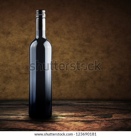 Wine bottle on wood floor with grunge wall background - stock photo