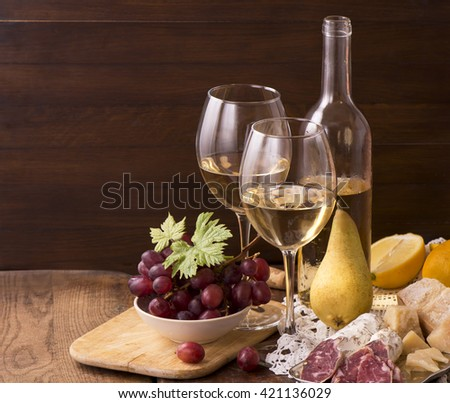 Wine bottle , Ripe grapes, wine glass and corks on wooden table