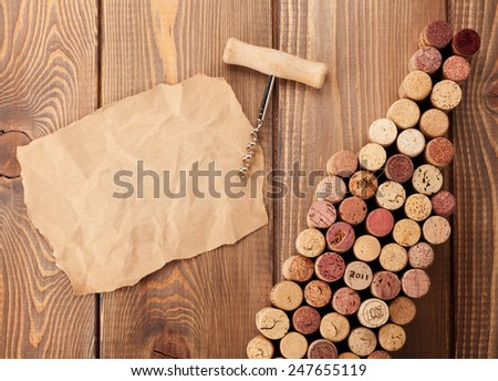 Wine bottle shaped corks, corkscrew and piece of paper for copy space over rustic wooden table background. Top view - stock photo