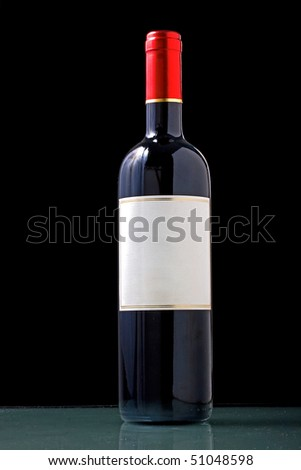 Wine bottle with blank paper generic tag on black background - stock photo