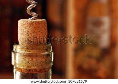 Wine bottle with corkscrew and partially removed cork.  Wine related decor in soft focus in background.  Macro with shallow dof. - stock photo