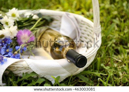 Wine bottle with flowers in basket on green grass