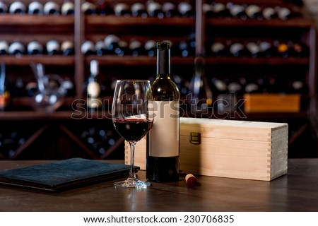 Wine bottle with glass and menu on the table at the wine cellar - stock photo