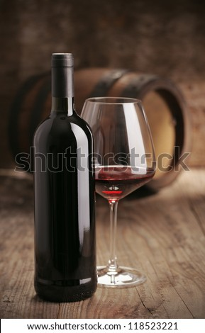 Wine bottle with glass,  barrel on background - stock photo