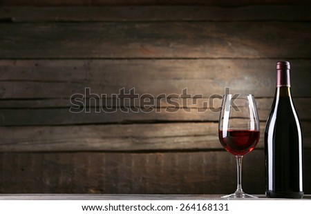 Wine bottle with glass on wooden background - stock photo