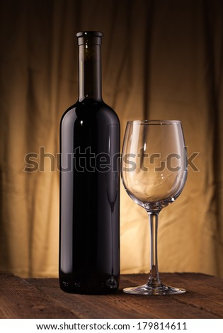 Wine bottle with glass on wooden table