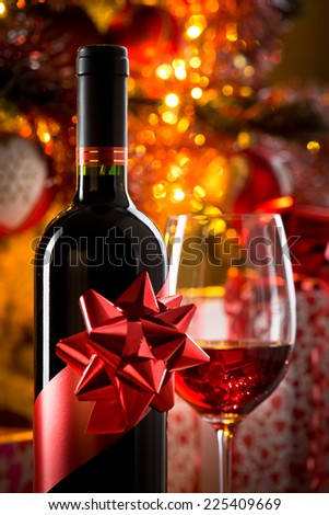 Wine bottle with ribbon and filled wineglass, christmas tree and gift boxes on background. - stock photo