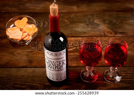 Wine bottle with self made label, glasses and heart shaped cookies on wooden table - stock photo