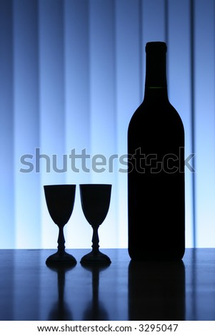 Wine bottle with two glasses, dramatic light, copy-space for text. - stock photo