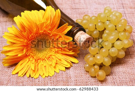 Wine bottle with yellow flower and grapes branch - stock photo