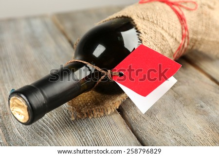 Wine bottle wrapped in burlap cloth on wooden planks background - stock photo