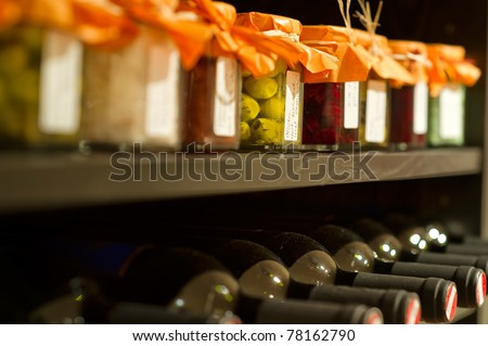 Wine bottles and mason jars in a shelf - stock photo